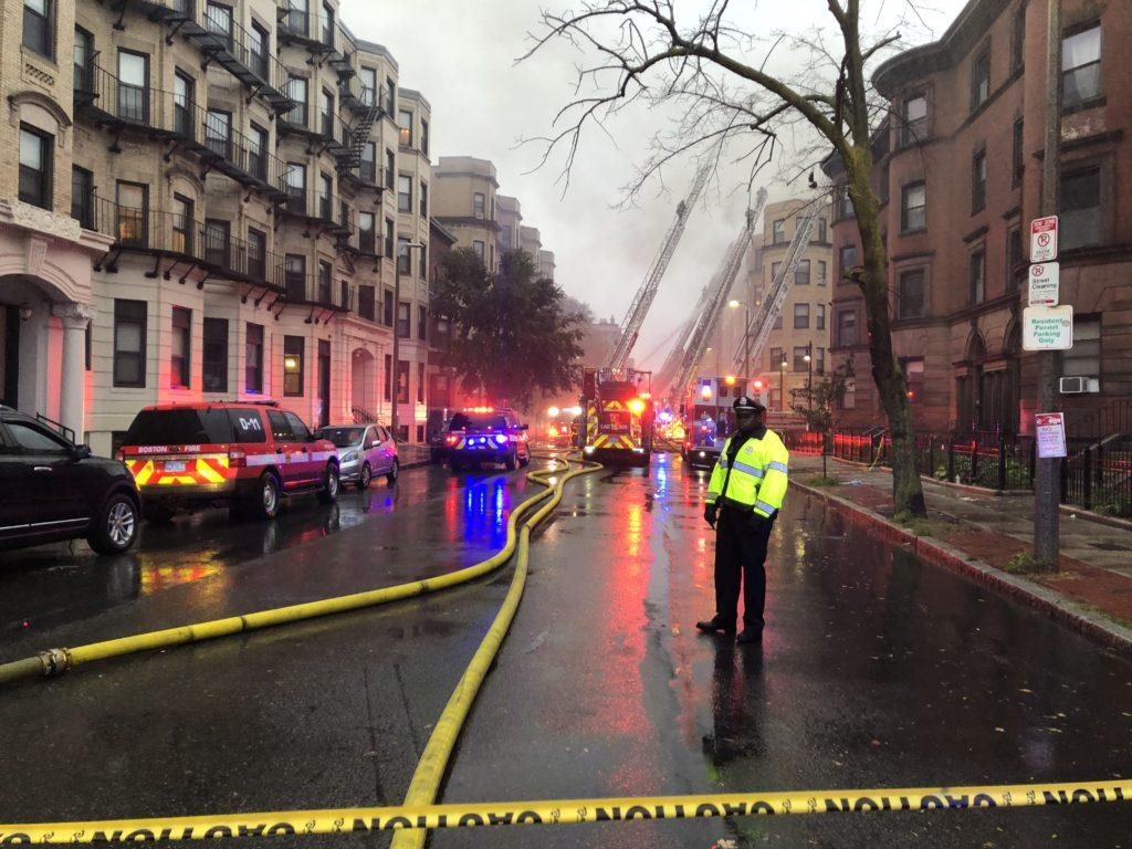 A Boston police officer stands watch as firefighters battle the seven alarm blaze at 104 Hemenway St. Oct. 27. Diana Bravo / Beacon Correspondent