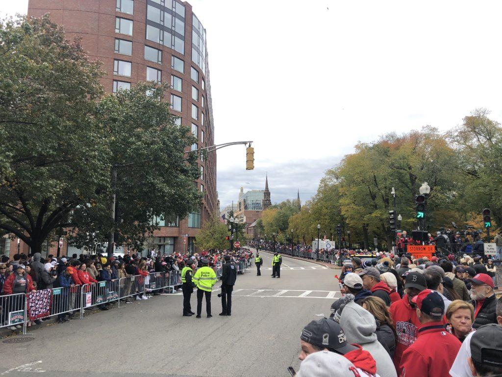 People lined up behind barricades on Wednesday as they wait for the parade to bass through Boylston St. Photo by Chris Van Buskirk / Beacon Staff.