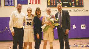Senior Charlie Boyle (second from right) is accompanied by her parents and sister, (second from left) sophomore Sam Boyle, during her senior day celebration. Photo by Maia Sperber / Beacon Staff