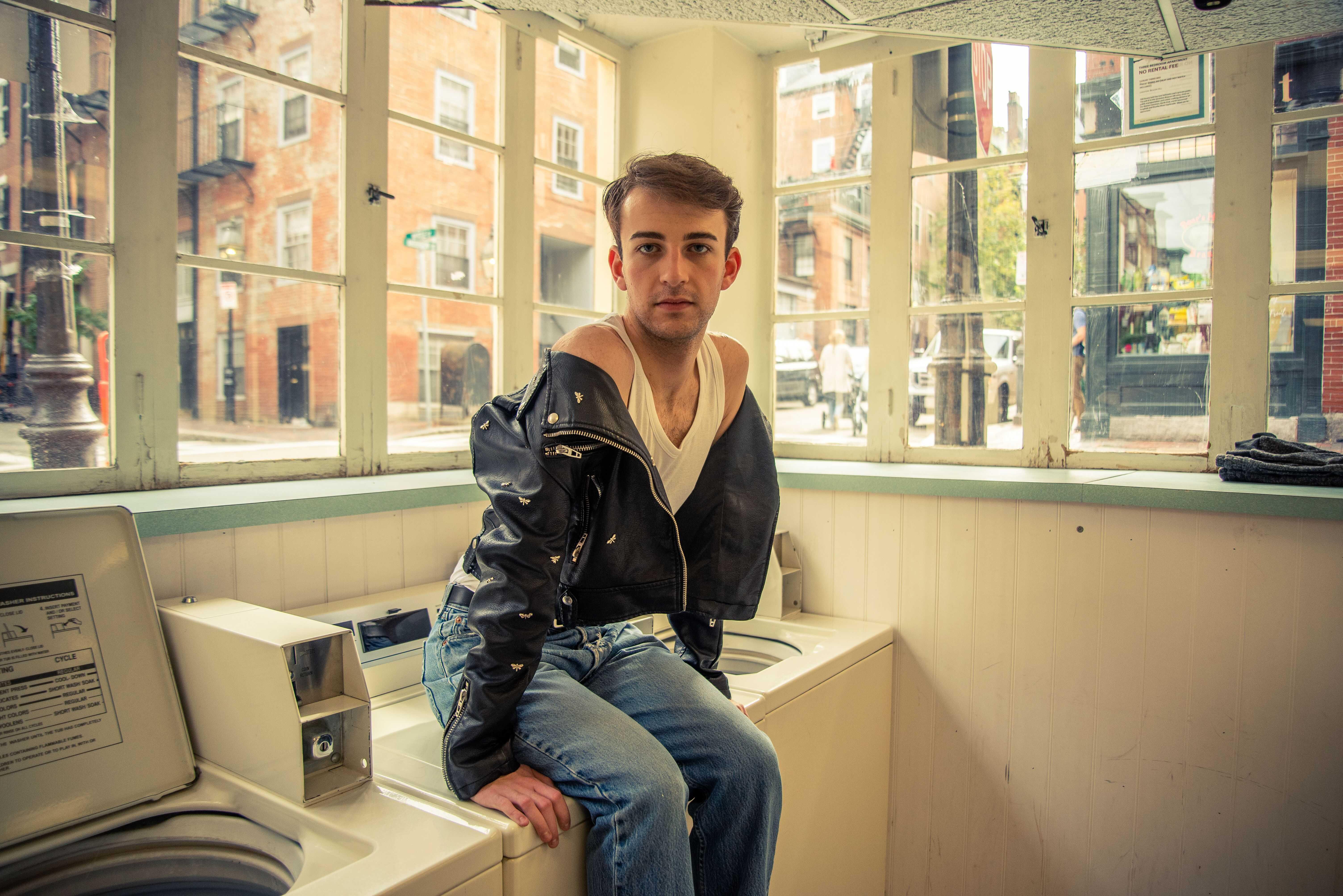 Junior Andrew Muccitelli sits atop a washing machine at Myrtle Street Laundromat. Jakob Menendez / Beacon Staff