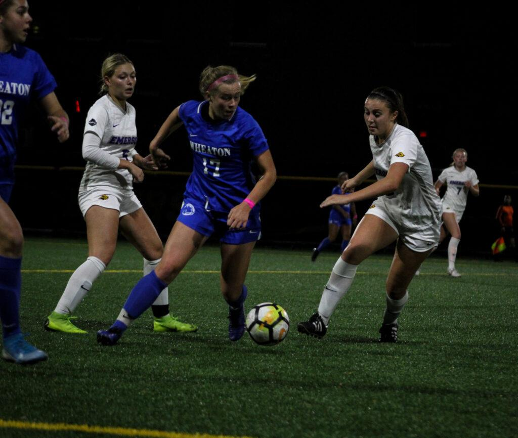 Sophomore Grace Cosgrove (second from left) and freshman Sage Stack (right) battle Wheaton defenders for the ball on Oct. 15. Rachel Culver / Beacon Staff