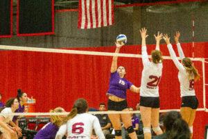 Freshman Rebecca Polsky hits the ball over the MIT blockers. Carol Rangel / Beacon Staff