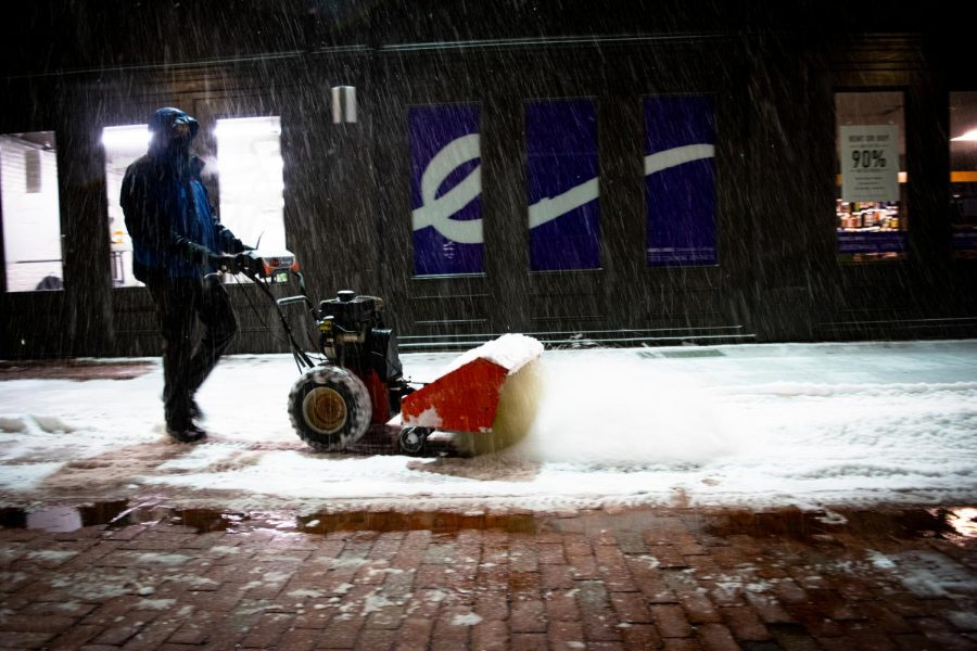 A snow blower clears the way for students to walk in the 2 Boylston Place alley.