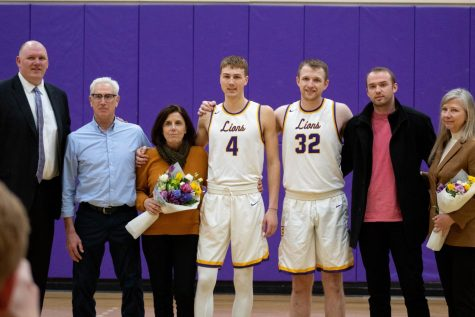 Coach Bill Curley (left) poses with Jack O'Connor (No. 4), Ben Holding (No. 32), and their family members during the pregame ceremony. Photo credit: Rachel Culver