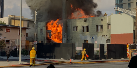 Firefighters attempt to extinguish a fire that broke out next to Emerson College's Los Angeles campus.