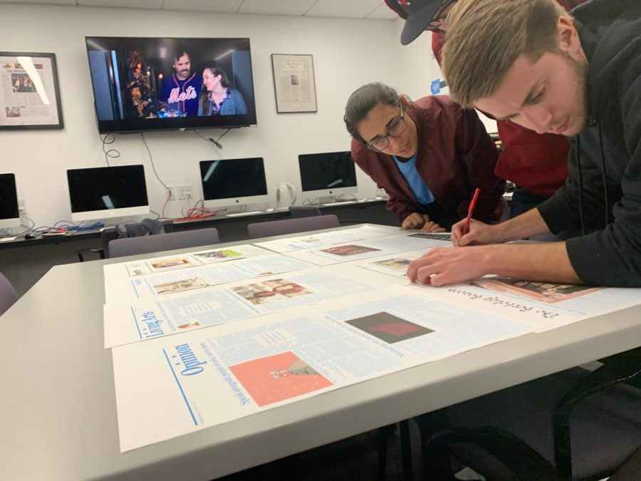 Former Managing Editors Abigail Hadfield and Kyle Bray proof the final version of The Beacon with former Editor Chris Van Buskirk.