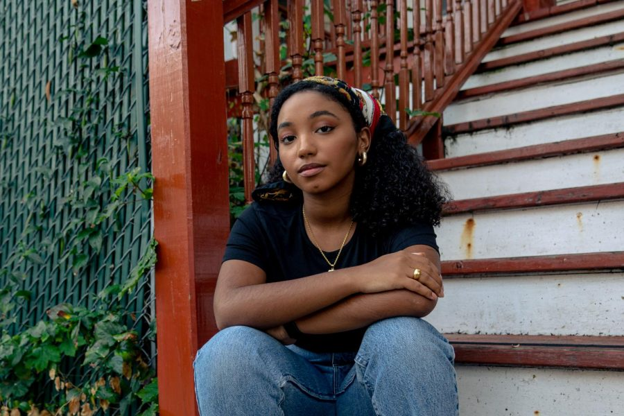 Zeiana Andrade sitting on the steps of her parents' Dorchester apartment.