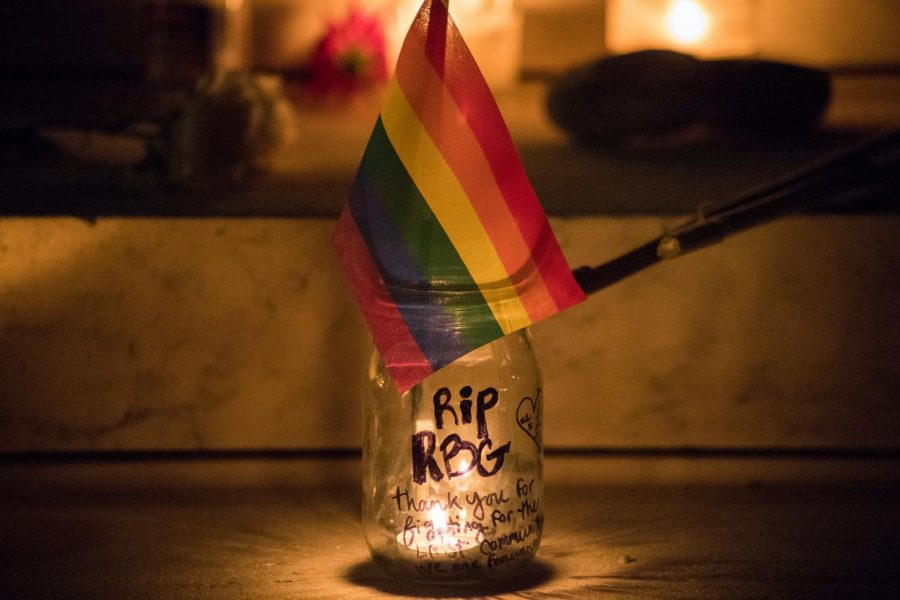 "A LQBTQ+ pride flag hangs over a jar displaying the phrase ""RIP RBG."""