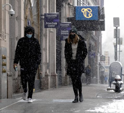 Students walk to The Little Building in the snow
