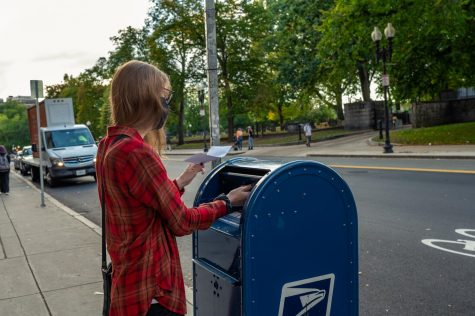 Tris Arthur dropping off her absentee ballot application in the mailbox outside of the Colonial Theater.