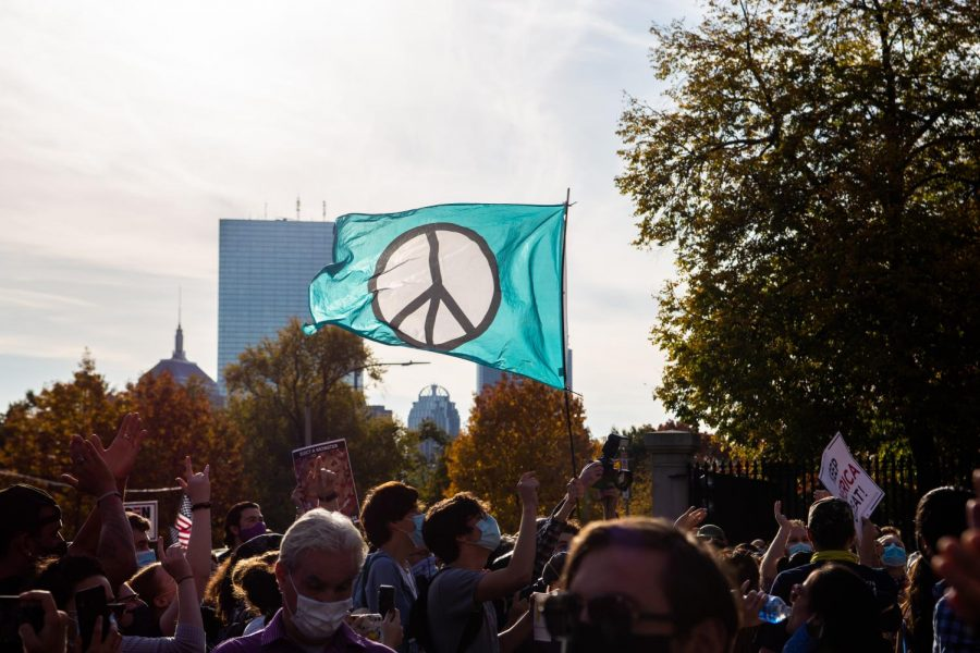 Demonstrates carry a peace sign flag on Boston Common in reaction to Joe Biden's presidential victory on Saturday, November 7, 2020.