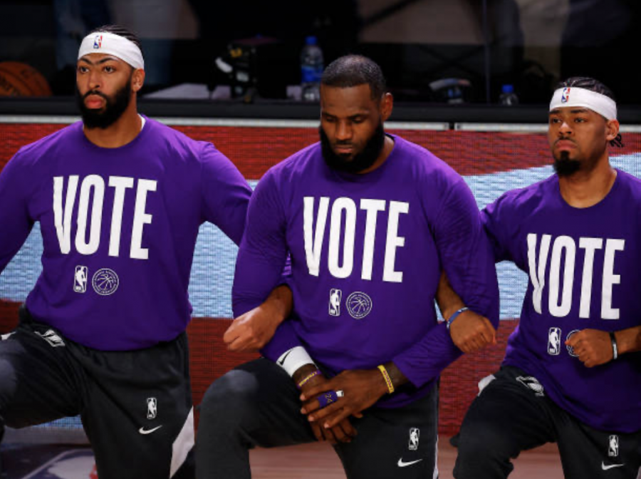 Lebron James and Lakers teammates kneel for the national anthem while wearing VOTE shirts.