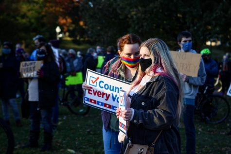 Two attendees listen to the Count Every Vote rally at Boston Common on Wednesday.