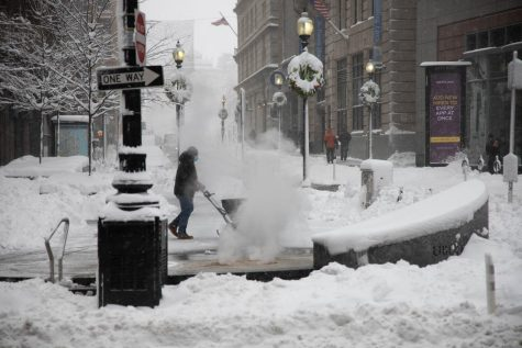 A worker dispensing salt along the Washington and Boylston Street intersection.