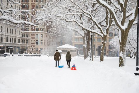 A couple sledding their child through the Boston Common.