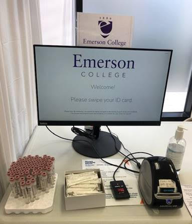 A computer where individuals tap their Emerson IDs, receive a label, and pick up a tube.