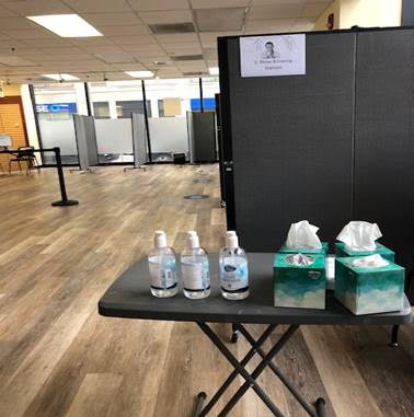 The screening and tissue station, where individuals are asked if they've had any COVID-19 symptoms and blow their nose.