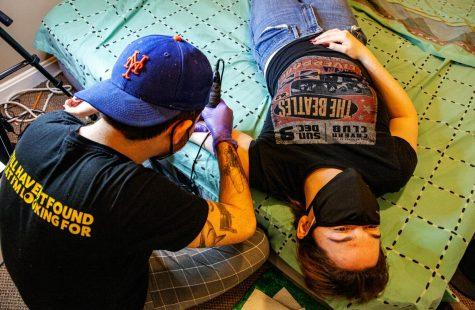 A client getting her tattoo on a mattress.