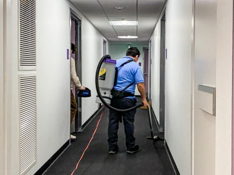 A janitor working in the dorm hallway.