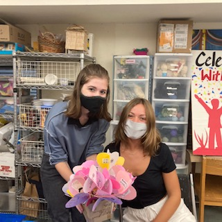 """Elly Bryant and Olivienne Redding at their volunteer shift holding """"kindness flower"""" made in the art studio for guests."""