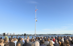 Attendees look on as the American Flag is lowered to half-staff at a memorial for the 20th anniversary of the Sept. 11 attacks.